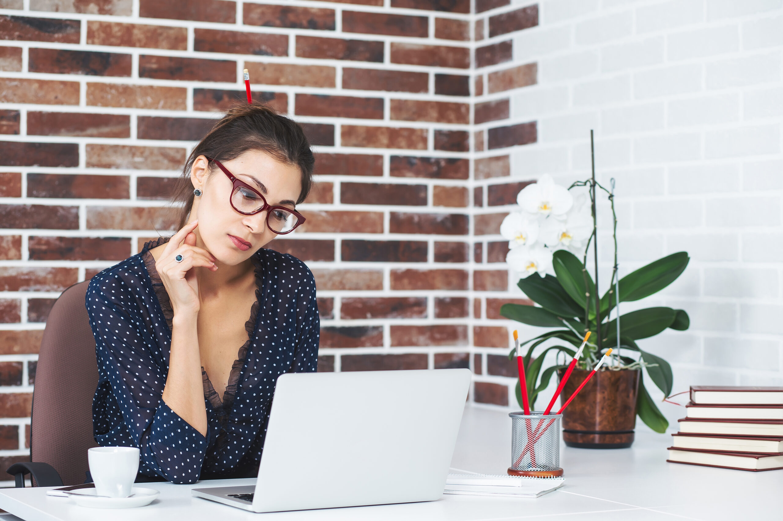 Business woman in the office at the desk with laptop